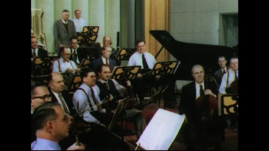 UNITED STATES 1950s: Musicians in orchestra stand, walk out with instruments.
