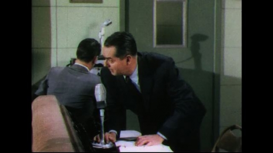 UNITED STATES 1950s: Man in sound booth speaks into microphone, other man walks into booth.