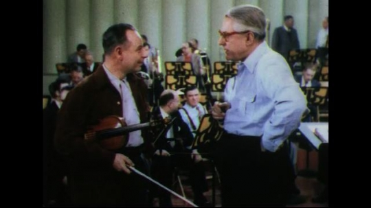 UNITED STATES 1950s: Conductor talks to violinist, zoom out / Conductor looks at music.