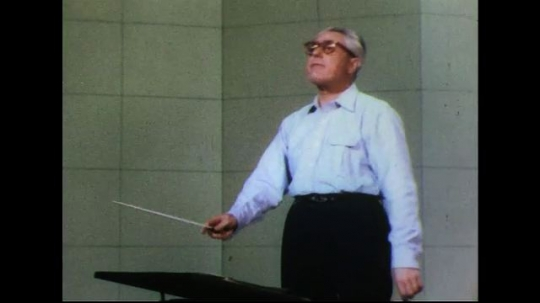 UNITED STATES 1950s: Conductor conducts at podium.