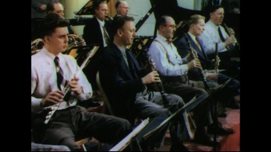UNITED STATES 1950s: Musicians in orchestra playing / Conductor conducting.