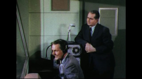 UNITED STATES 1950s: Men is sound booth, man claps / Man takes reel from tape recorder, lifts machine.