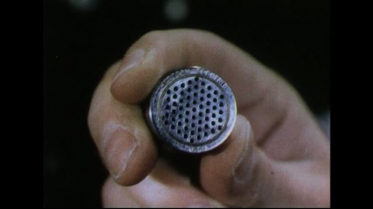 UNITED STATES 1950s: Close up of small microphone in hand / Man looks at microphone.