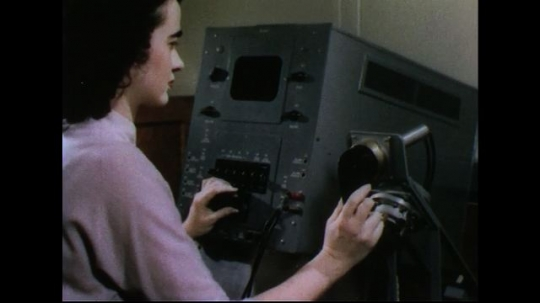 UNITED STATES 1950s: Woman takes phone receiver off of machine / Receiver put on rack, takes another receiver / Receiver placed on machine / Woman at machine / Electronic sound waves on gauge