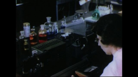 UNITED STATES 1950s: Woman in lab, pan up to men talking, man talks to woman / Woman adjusts equipment.
