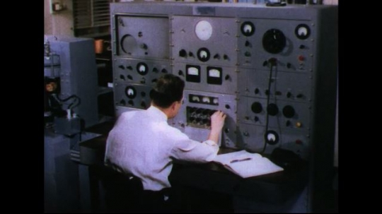 UNITED STATES 1950s: Man sitting at equipment / Man adjusts dial, moves to other side of desk.