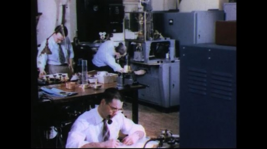 UNITED STATES 1950s: Pan of lab, researchers / Man looks at machine / Machine part moving / Close up of part.