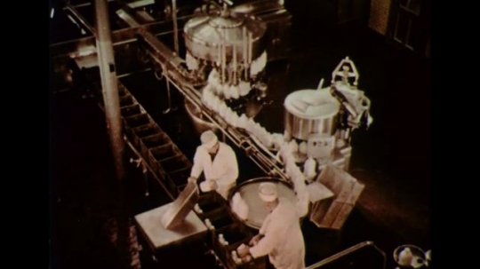 UNITED STATES 1950s: Milk is packaged in a factory and later delivered by the milk man to households.