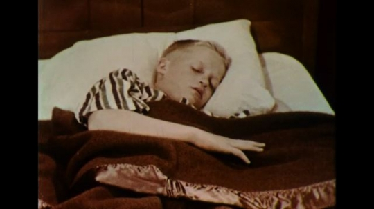 UNITED STATES 1950s: A boy opens his eyes from his bed as a newspaper boy throws the day
