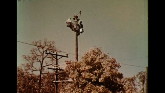 UNITED STATES 1950s: Linemen fix electric hardware on top of a pole.