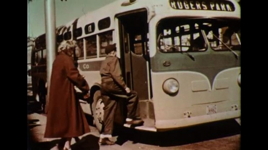 UNITED STATES 1950s: Passengers get on a bus at a stop.