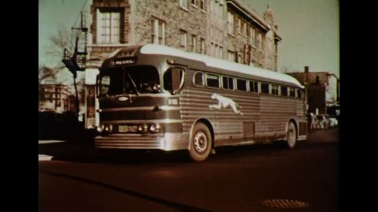 UNITED STATES 1950s: A Greyhound bus stops in a city near a railroad track.