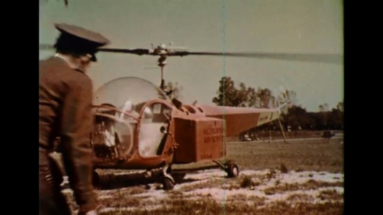 UNITED STATES 1950s: A mail man places mail on the storage bin of a helicopter.