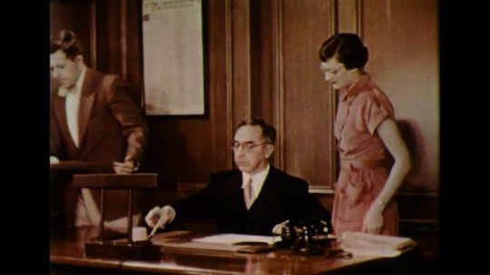 UNITED STATES 1950s: In a government office, a public figure signs papers as his secretary waits next to him.