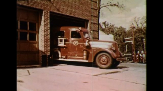 UNITED STATES 1950s: Fire trucks leave a station ringing their alarms to signal an emergency.