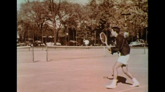 UNITED STATES 1950s: Adults play tennis as children go to a recreation center.
