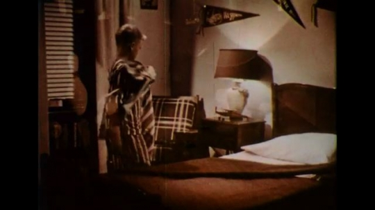 UNITED STATES 1950s: A boy in his pajamas turns off a bedside lamp and goes to bed.