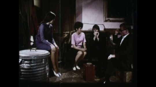 UNITED STATES 1960s: A man and three women sit in a back alley and pass around blunt.