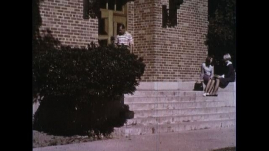 UNITED STATES 1960s: A man walks down the steps of a building in his school an receives a D on a quiz.