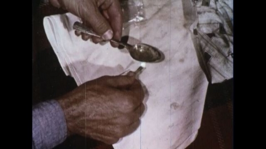 UNITED STATES 1960s: The narcotic is dissolved by applying heat to the spoon and filtered into a syringe which is then attached to a needle.