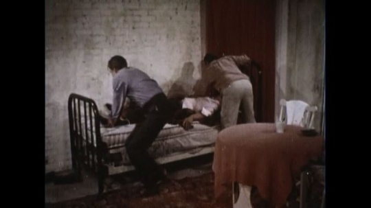UNITED STATES 1960s: Two men tie the young bad to the bed posts as he continues having convulsions and frothing at the mouth.