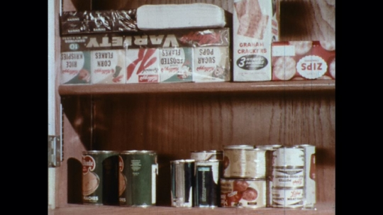 UNITED STATES: 1960s: tin food on shelf. Hand cleans tin can.