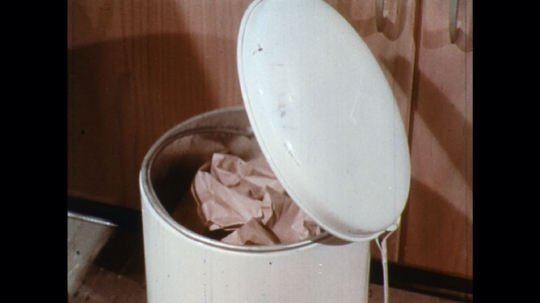 UNITED STATES: 1960s: disposal of paper towel in bin. Hand opens tin can.
