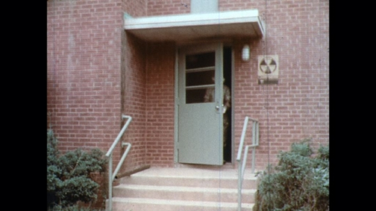 UNITED STATES: 1960s: man leaves fallout shelter in coat.