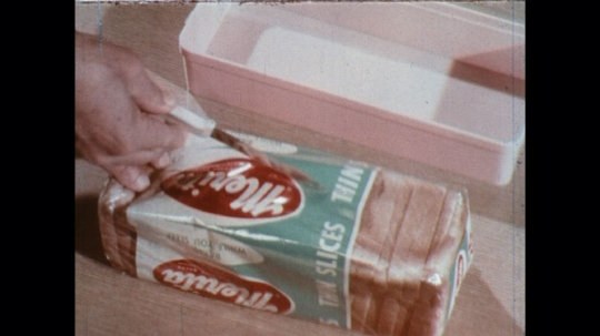 UNITED STATES: 1960s: loaf of bread in packaging. Hand opens bread packaging safely.