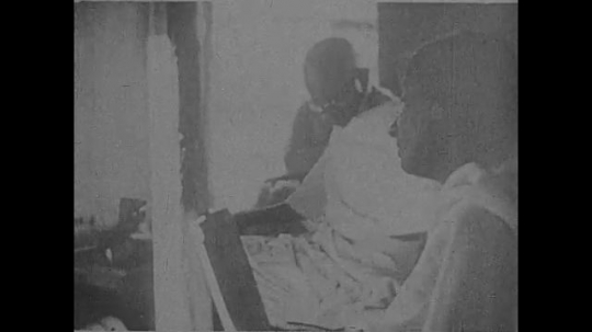 INDIA- CIRCA 1930: Gandhi sits and works with thread.  A large crowd of men in topis and mundus look up at Gandhi, who sits on a small stage.  A large crowd of women in saaris and children sit.