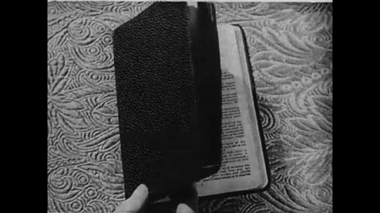 A hand flips open a Bible, written in English, which sits on top of an intricately designed cloth, to the Book of Matthew.  A beam of light illuminates the center of the page.