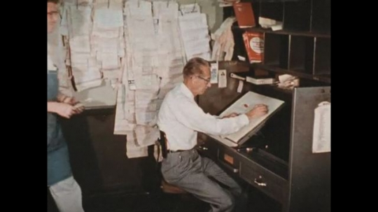 UNITED STATES 1960s: The editor is handed short articles which he proofreads.