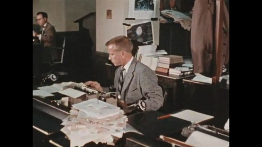 UNITED STATES 1960s: Writers continue reading in the newsroom to get ideas for their articles.
