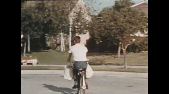 UNITED STATES 1960s: Paper boy delivers papers to houses and establishments in a roundabout until the newspaper reaches the hands of the barbershop clients.