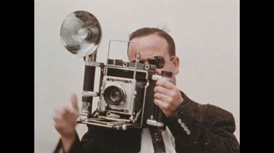 UNITED STATES 1960s: Photographer takes several pictures with his SLR while holding up his flash light.