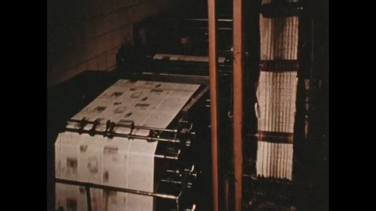 UNITED STATES 1960s: Worker at the printing company pulls finished paper from the  printing press.