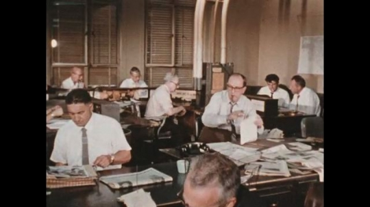 UNITED STATES 1960s: Working writers at the office pass their articles to be proofread by editor.