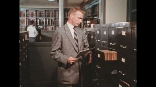 UNITED STATES 1960s: Writer goes through the archive to read previously written articles and picture about elephant.