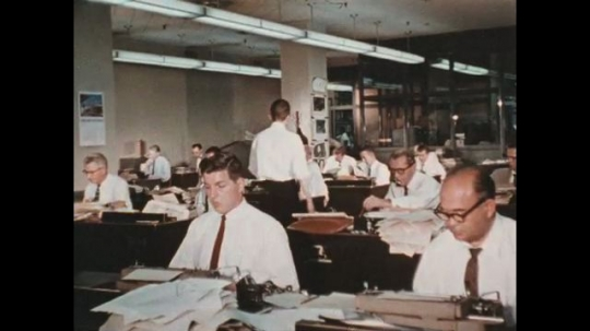 UNITED STATES 1960s: As reporters are busy writing their articles, one man looks up at the clock which is about to turn 6 o