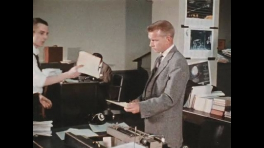 UNITED STATES 1960s: Writer typing story after receiving information from his colleague.