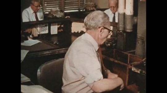 UNITED STATES 1960s: Paperwork is sent through a pneumatic tube system which arrives at another site in the newspaper company.