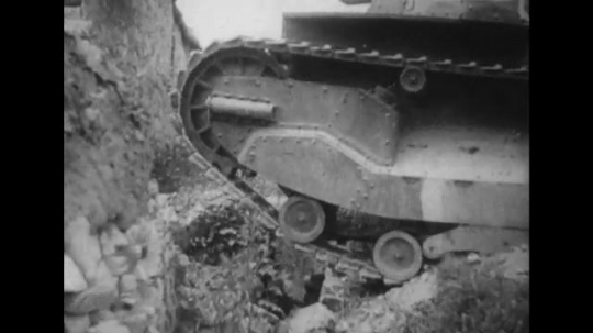 UNITED STATES 1940s: Close up, tread of tank / Tank enters village gate / Long shots of soldiers marching / Soldiers climb up mountain / Soldiers climb rocks.