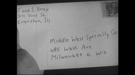 UNITED STATES 1950s : After checking and sealing, a girl gives an envelope to her brother who drops it into a mailbox.