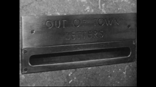 UNITED STATES 1950s : Letters going out of town are dropped on a mailbox into a tray that is piling up.