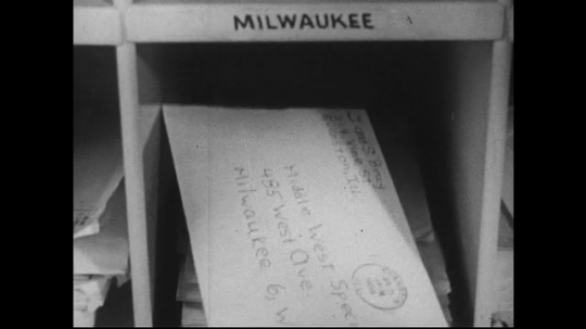 UNITED STATES 1950s : As letters start to fill a case in the post office, they are bundled by a machine.