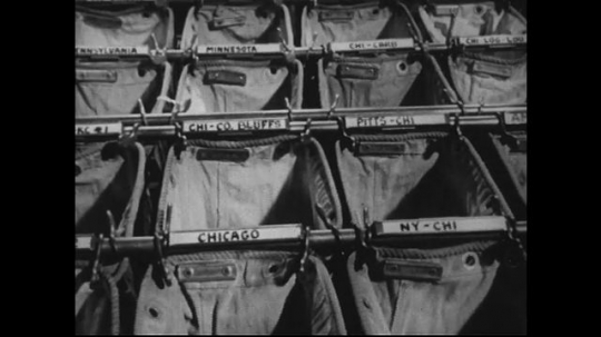 UNITED STATES 1950s : Bundles of letters in the post office are placed inside pouches based on their destination.