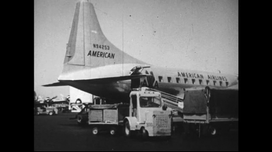 UNITED STATES 1950s : Pouches and sacks of mail are loaded into planes and trains to bring them to their city or town of destination.