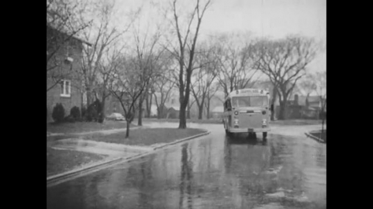 UNITED STATES: 1950s: Siblings run outside their house to catch a school bus in the rain.