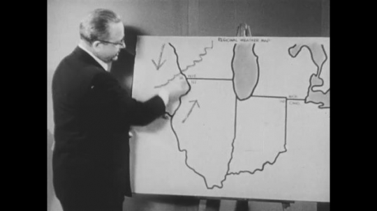 UNITED STATES: 1950s: man points to map and draws lines to show weather.