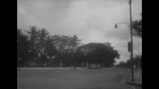 UNITED STATES 1940s: Street in Honolulu / Japanese planes in air / Beach scene, mountains.